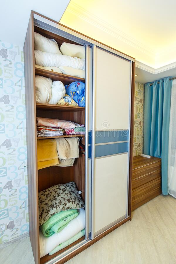 Open Built-in wardrobe with bedding. There is a chest of drawers next to it royalty free stock photography