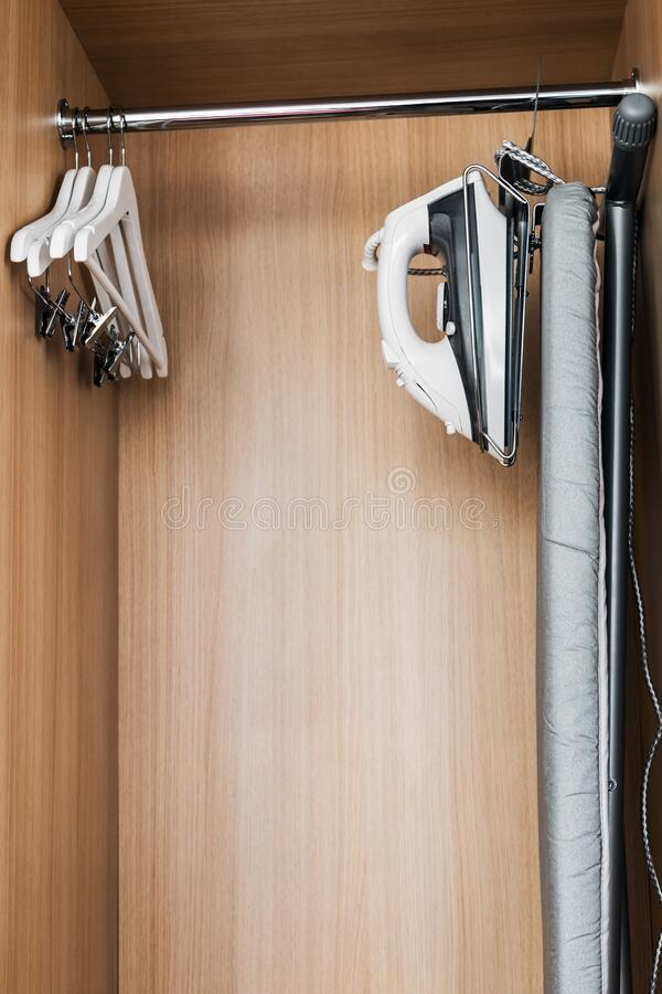 Wardrobe with wooden hangers and built-in Ironing station royalty free stock image